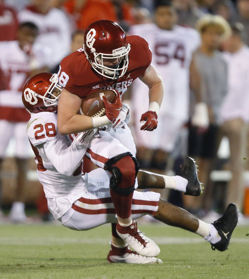 Photo - Oklahoma's Austin Stogner (18) is brought down by Oklahoma's Chanse Sylvie (28) during the University of Oklahoma's (OU) spring football game at Gaylord Family-Oklahoma Memorial Stadium in Norman, Okla., Friday, April 12, 2019. Photo by Bryan Terry, The Oklahoman