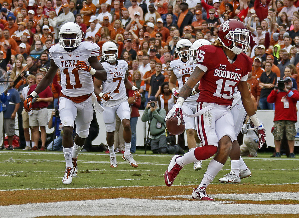 Photo - Oklahoma's Zack Sanchez (15) returns an interception for a touchdown in front of Texas' Jacorey Warrick (11) and Marcus Johnson (7) during the Red River Showdown college football game between the University of Oklahoma Sooners (OU) and the University of Texas Longhorns (UT) at the Cotton Bowl in Dallas on Saturday, Oct. 11, 2014. 