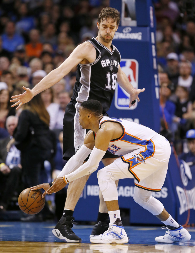 Photo - Oklahoma City's Russell Westbrook (0) passes around San Antonio's Pau Gasol (16) during an NBA basketball game between the Oklahoma City Thunder and San Antonio Spurs at Chesapeake Energy Arena in Oklahoma City, Friday, March 31, 2017. Photo by Nate Billings, The Oklahoman