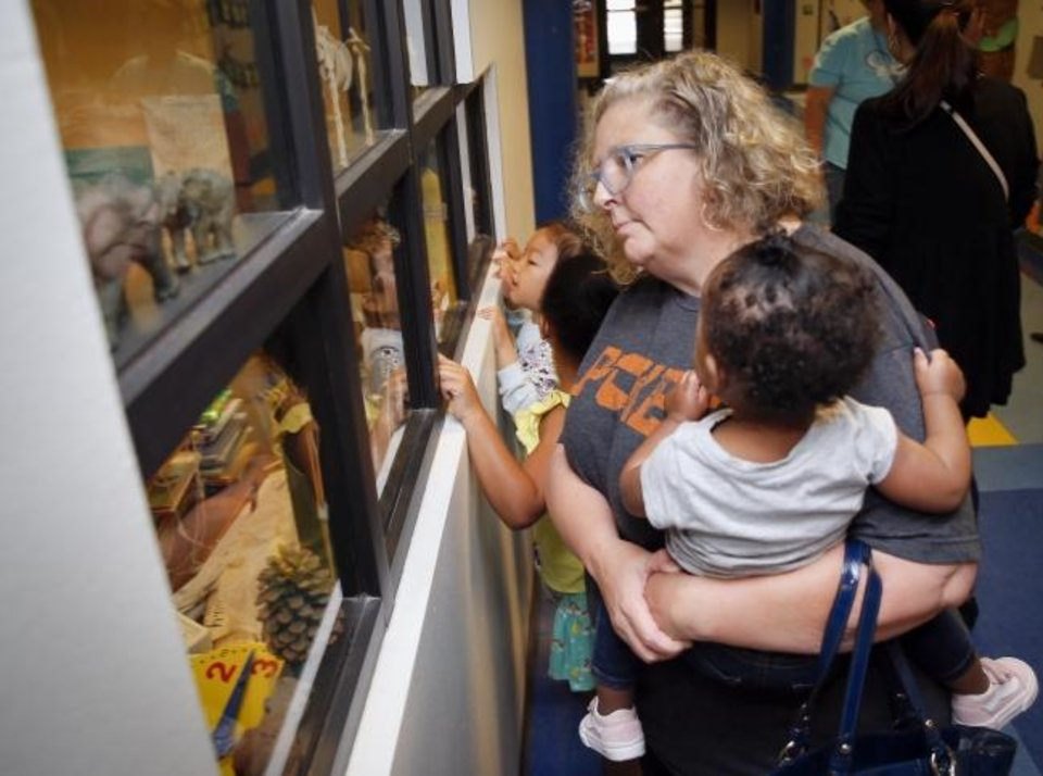 Photo -  Patty Brimacombe, front, looks in the window of a classroom Saturday with her daughter Makylah McFrazier, 6, middle, and fellow student Coco Chen, 6, back, as she holds her nephew Zuri Echols, during a POP-IN Open House for Oklahoma City Public Schools at Eugene Field Elementary. The open houses across the district gave families who will be changing schools next year a chance to tour their new school and meet the principal. Makylah McFrazier and Coco Chen attend Gatewood now and will be in first grade next year. [Nate Billings/The Oklahoman]
