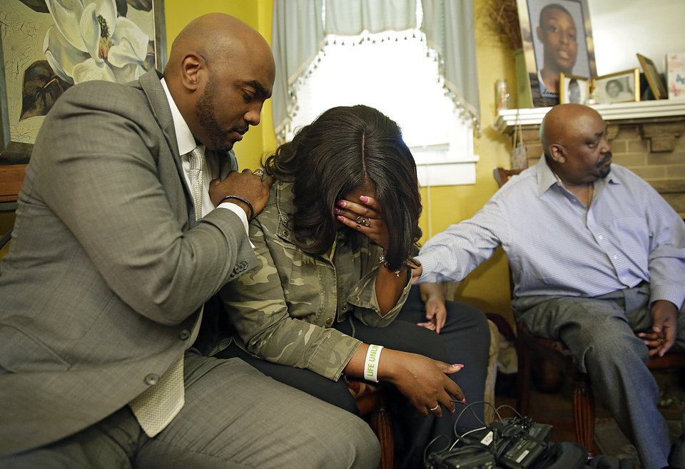 Photo - Attorney Damario Solomon-Simmons(left) comforts Tiffany Crutcher, twin sister of Terence Crutcher who was shot and killed by Tulsa Police Friday night. At right is Rev. Joey Crutcher, her and Terence's father. MIKE SIMONS/Tulsa World