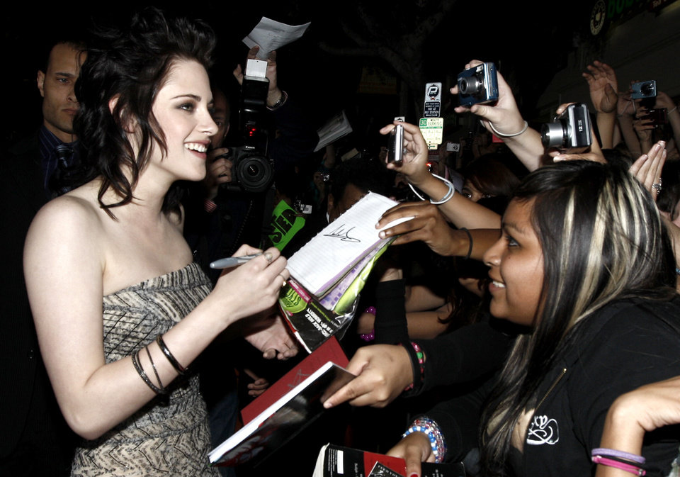 Photo - Actress Kristen Stewart signs autographs as she arrives at The Twilight Saga: New Moon premiere in Westwood, Calif. Monday, Nov. 16, 2009.  (AP Photo/Matt Sayles) ORG XMIT: CAGS141