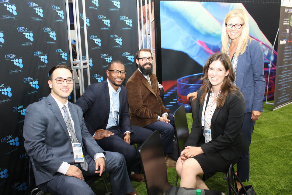 Photo -  University of Oklahoma Venture Fellows, from left, Blake Hopiavuori, Cortes Williams and Dustin Masser, are shown with Meredith Wilkerson, technology development associate in OU's Office of Technology Development, and Gina McMillen, director of OU's Office of Technology Development. The group is at the Oklahoma biosciences booth at the 2017 BIO show in San Diego.