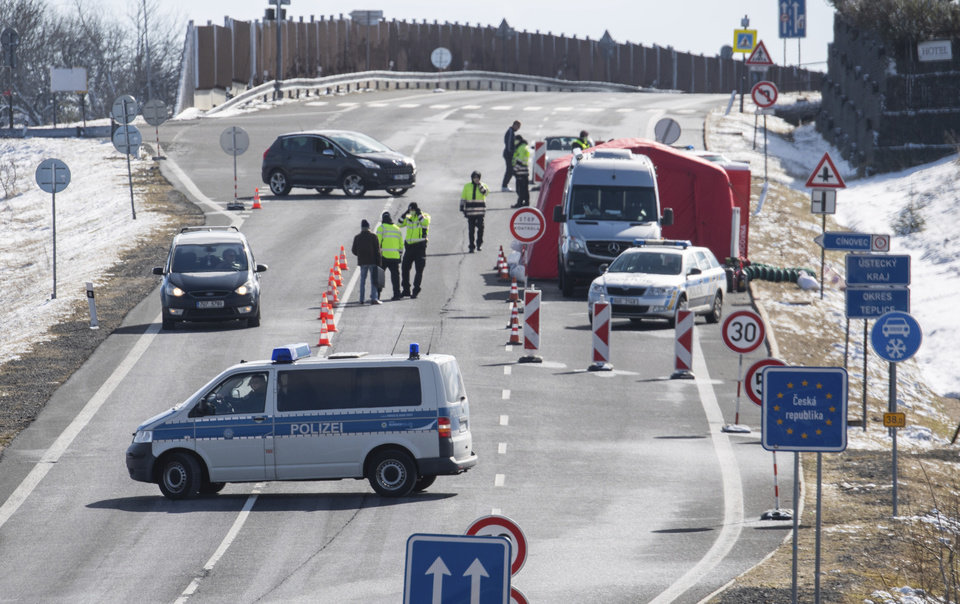 Photo -  Czech policemen are standing on a street at the Czech border for entry control near Zinnwald, Germany, Saturday, March 14, 2020. The Czech Republic largely closes its borders to foreigners from several European countries. Among others, citizens from Germany, Italy, France and Austria who do not have a permanent residence in the EU member state are affected. (Robert Michael/dpa via AP)