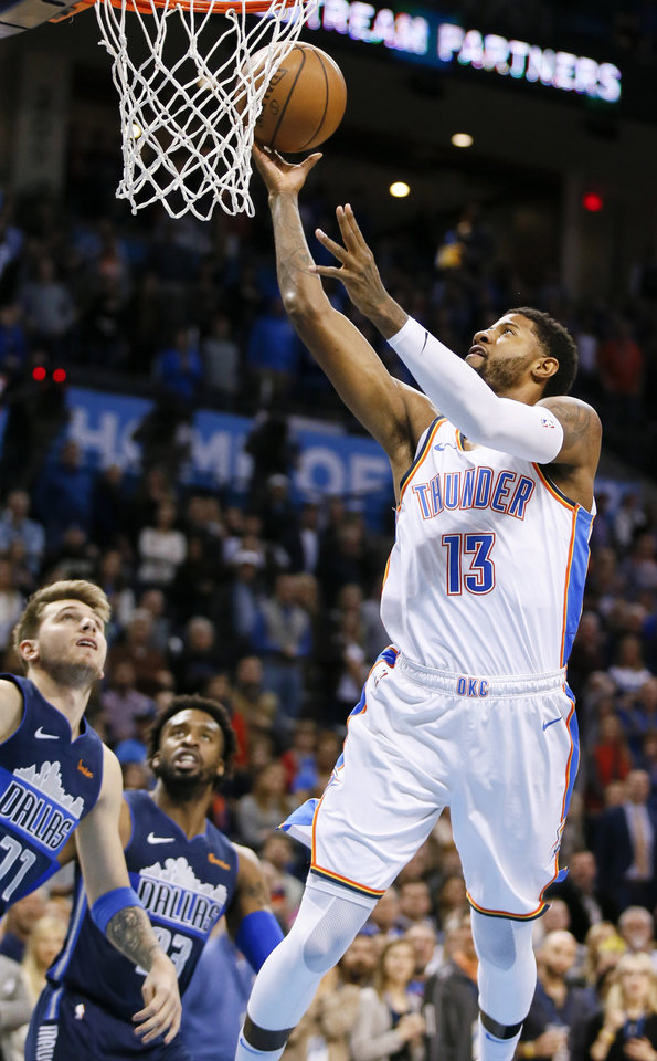 Photo - Oklahoma City's Paul George (13) shoots next to Dallas' Luka Doncic (77) and Wesley Matthews (23) during an NBA basketball game between the Oklahoma City Thunder and Dallas Mavericks at Chesapeake Energy Arena in Oklahoma City, Monday, Dec. 31, 2018. Photo by Nate Billings, The Oklahoman