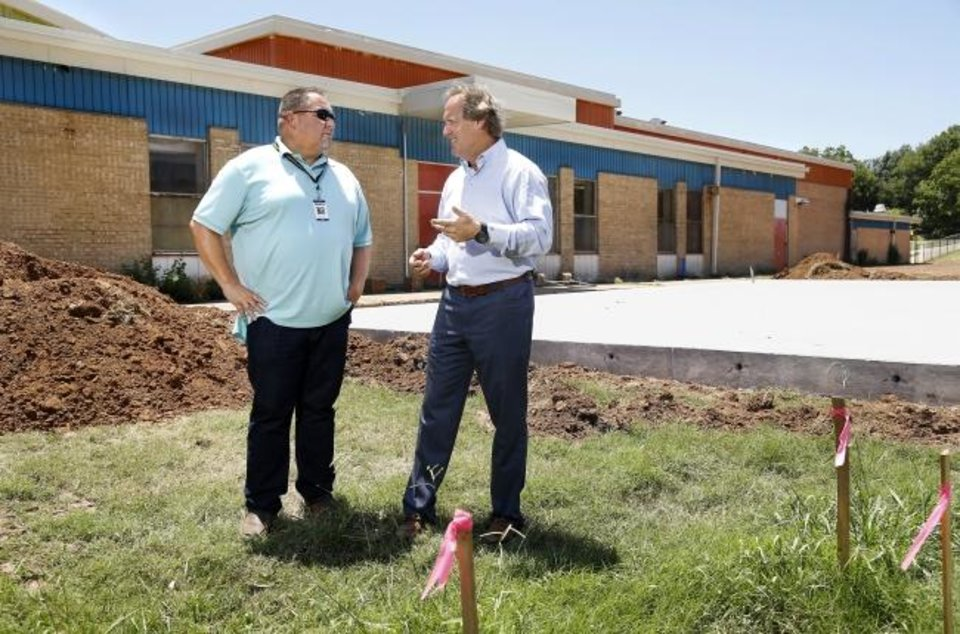Photo -  Todd Dilbeck, left, athletic director for Oklahoma City Public Schools, talks with Tim McLaughlin, Fields & Futures founder, in an open field behind F. D. Moon Middle School. Fields & Futures has begun renovations at seven middle schools in Oklahoma City to build athletic fields and courts. [Jim Beckel/The Oklahoman]