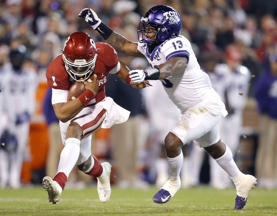 Photo - Oklahoma's Jalen Hurts (1) tries to get by Dee Winters (13) in the third quarter during an NCAA football game between the University of Oklahoma Sooners (OU) and the TCU Horned Frogs at Gaylord Family-Oklahoma Memorial Stadium in Norman, Okla., Saturday, Nov. 23, 2019. OU won 28-24. [Sarah Phipps/The Oklahoman]