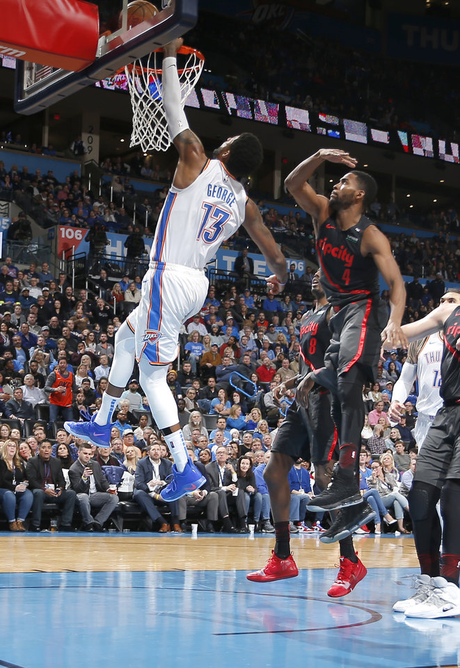 Photo - Oklahoma City's Paul George (13) goes up for a lay up in front of Portland's Maurice Harkless (4) and Al-Farouq Aminu (8) during the NBA basketball game between the Oklahoma City Thunder and the Portland Trail Blazers at Chesapeake Energy Arena in Oklahoma City, Tuesday, Jan. 22, 2019. Photo by Sarah Phipps, The Oklahoman