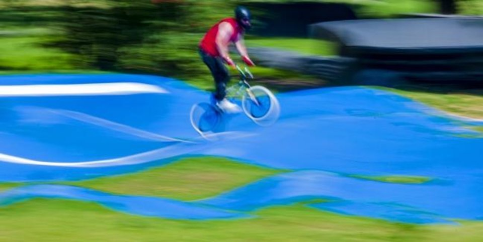 Photo -  A cyclist rides the blue rollers of the pump track Monday at Riversport OKC.   [Chris Landsberger/The Oklahoman]