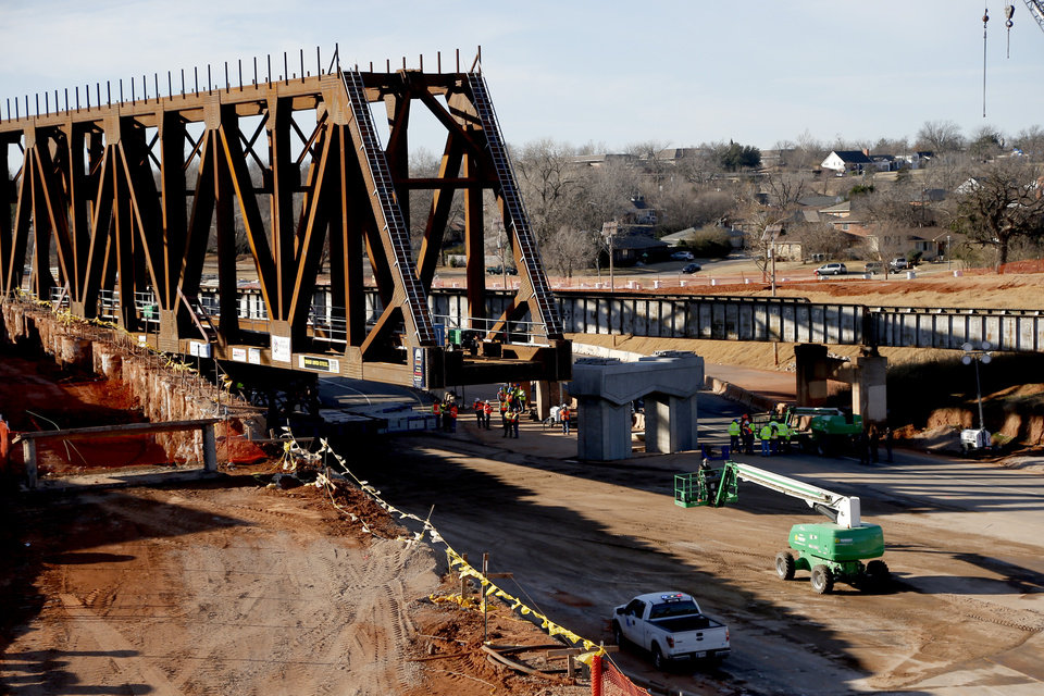 Photo -  Workers install the new railroad bridge over Interstate 235 in Oklahoma City. [Photo by Sarah Phipps, The Oklahoman]