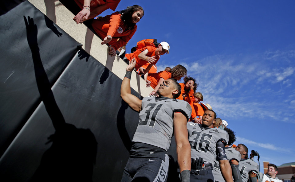 Photo - Oklahoma State's Kolby Harvell-Peel (31) celebrates with fans following the college football game between the Oklahoma State University Cowboys and the Kansas Jayhawks at Boone Pickens Stadium in Stillwater, Okla., Saturday, Nov. 16, 2019. OSU won 31-13. [Sarah Phipps/The Oklahoman]