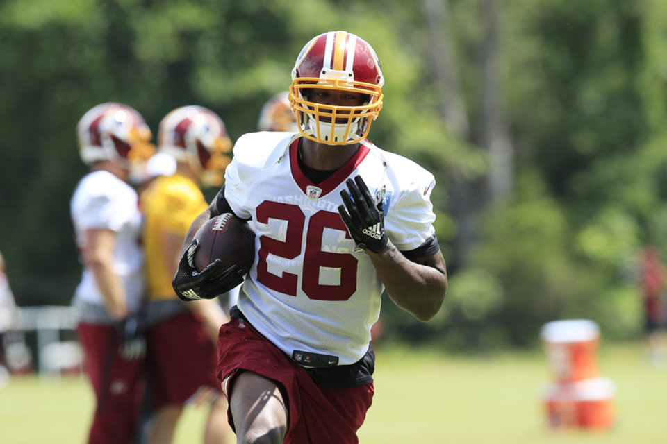 Photo - Washington Redskins running back Adrian Peterson (26) runs with the ball during an NFL football minicamp at Redskins Park in Ashburn, Va., Thursday, June 6, 2019. (AP Photo/Manuel Balce Ceneta)