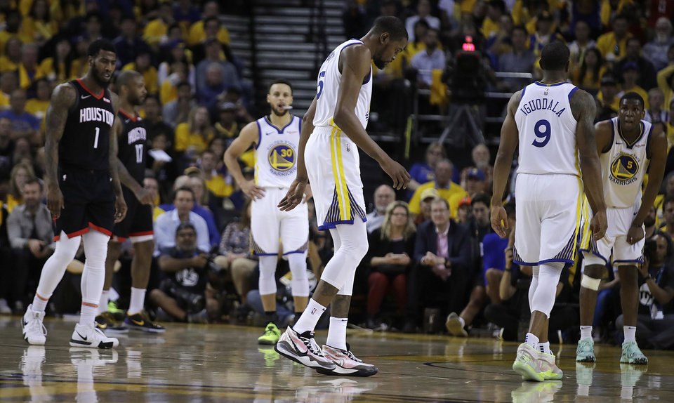 Photo - Golden State Warriors' Kevin Durant, center, limps off the court during the second half of Game 5 of the team's second-round NBA basketball playoff series against the Houston Rockets on Wednesday, May 8, 2019, in Oakland, Calif. (AP Photo/Ben Margot)