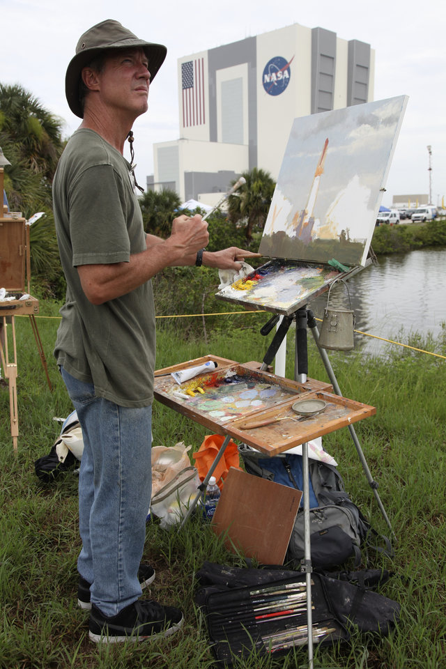Photo -  FILE - In this Friday, July 8, 2011 file photo, artist Larry Moore paints the scene at the Kennedy Space Center in Cape Canaveral, Fla., during the launch of the Atlantis, the 135th and final space shuttle mission for U.S. (AP Photo/Robert Ray)