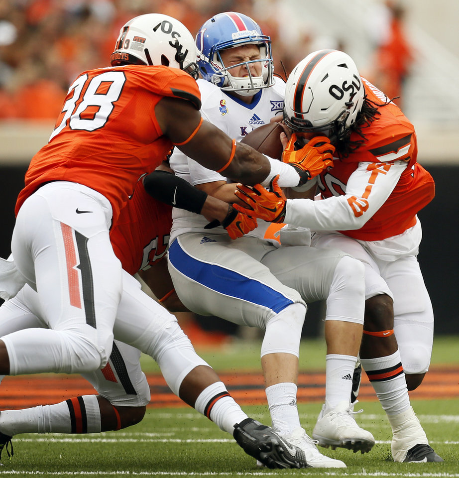 Photo - Kansas' Ryan Willis (13) is sacked by Oklahoma State's Jordan Burton (20), right, Emmanuel Ogbah (38), left, and Miketavius Jones (24), back left, during a college football game between the Oklahoma State University Cowboys (OSU) and the Kansas Jayhawks (KU) in Stillwater, Okla., Saturday, Oct. 24, 2015. Photo by Nate Billings, The Oklahoman