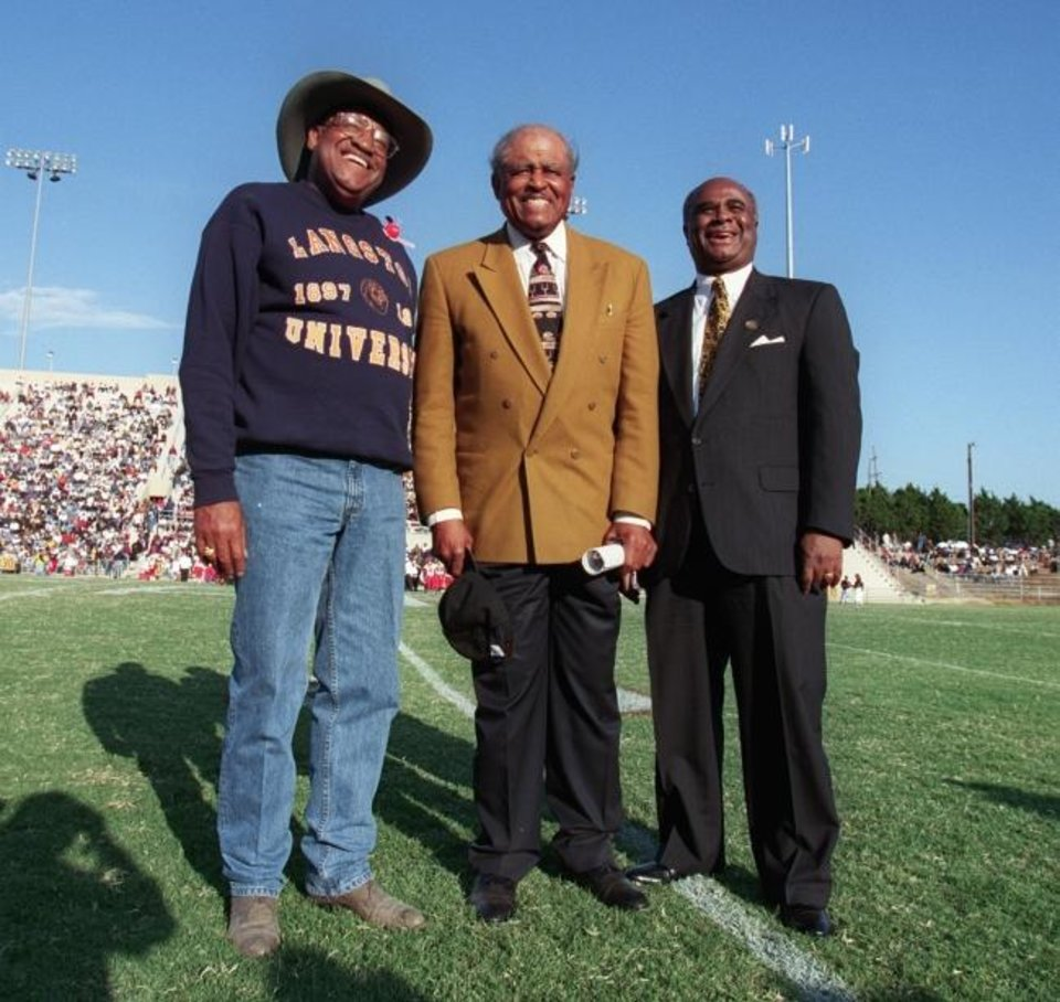 Photo -  Langston president Ernest Holloway and Grambling coach Eddie Robinson and Grambling president Dr. Raymond Hicks pose before the standing room only crowd at Taft Stadium in 1997. [OKLAHOMAN ARCHIVES]