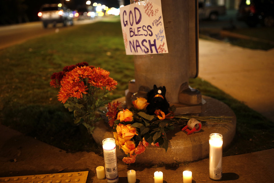 Photo - A memorial at Main and Hall of Fame is pictured where earlier a car crashed into spectators during the Oklahoma State University homecoming parade killing 4 people and injured several in Stillwater, Okla., Saturday, Oct. 24, 2015. Photo by Sarah Phipps, The Oklahoman