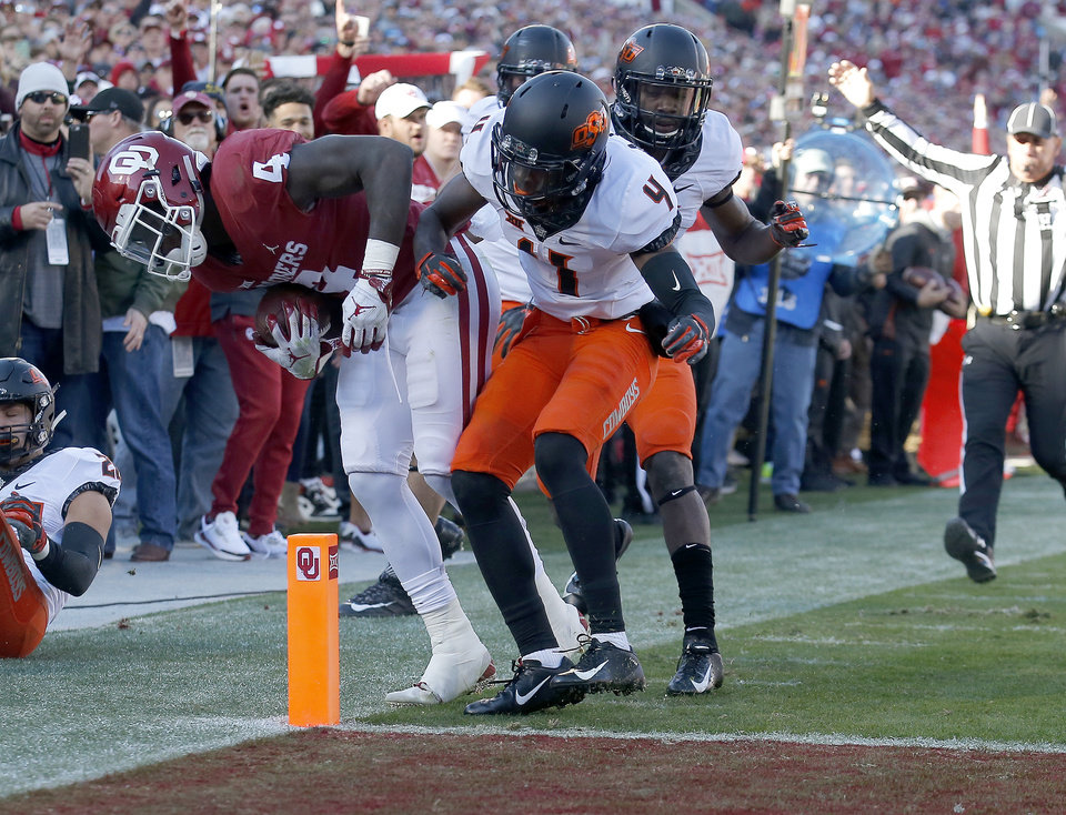 Photo - Oklahoma State's A.J. Green (4) pushes Oklahoma's Trey Sermon (4) out of bounds before he can score in the second quarter during a Bedlam college football game between the University of Oklahoma Sooners (OU) and the Oklahoma State University Cowboys (OSU) at Gaylord Family-Oklahoma Memorial Stadium in Norman, Okla., Nov. 10, 2018.  Photo by Sarah Phipps, The Oklahoman