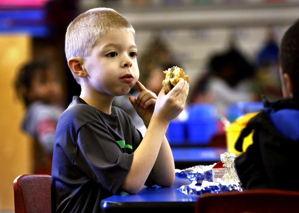 Photo -  Highland Park Elementary pre-k student Marcus Evans eats breakfast as part of the new Breakfast in the Classroom program. [Photos by Steve Sisney, The Oklahoman]
