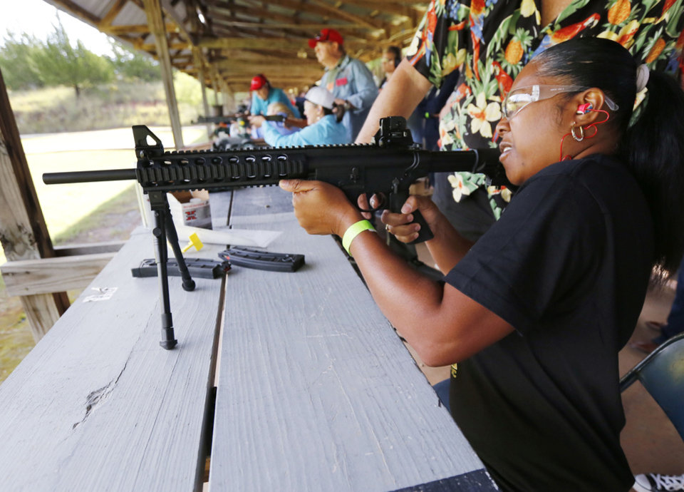 Photo -  Elaine Cheatham shoots an AR style .22 rifle. (Photo by Paul Hellstern, The Oklahoman)