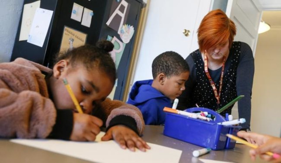 Photo -  Second-grader Jayden, 7, gets help from art and music teacher Sarah Caputo next to Myrakle, 7, left, during art class at Positive Tomorrows school for homeless children in Oklahoma City, Wednesday, Jan. 23, 2019. Photo by Nate Billings, The Oklahoman