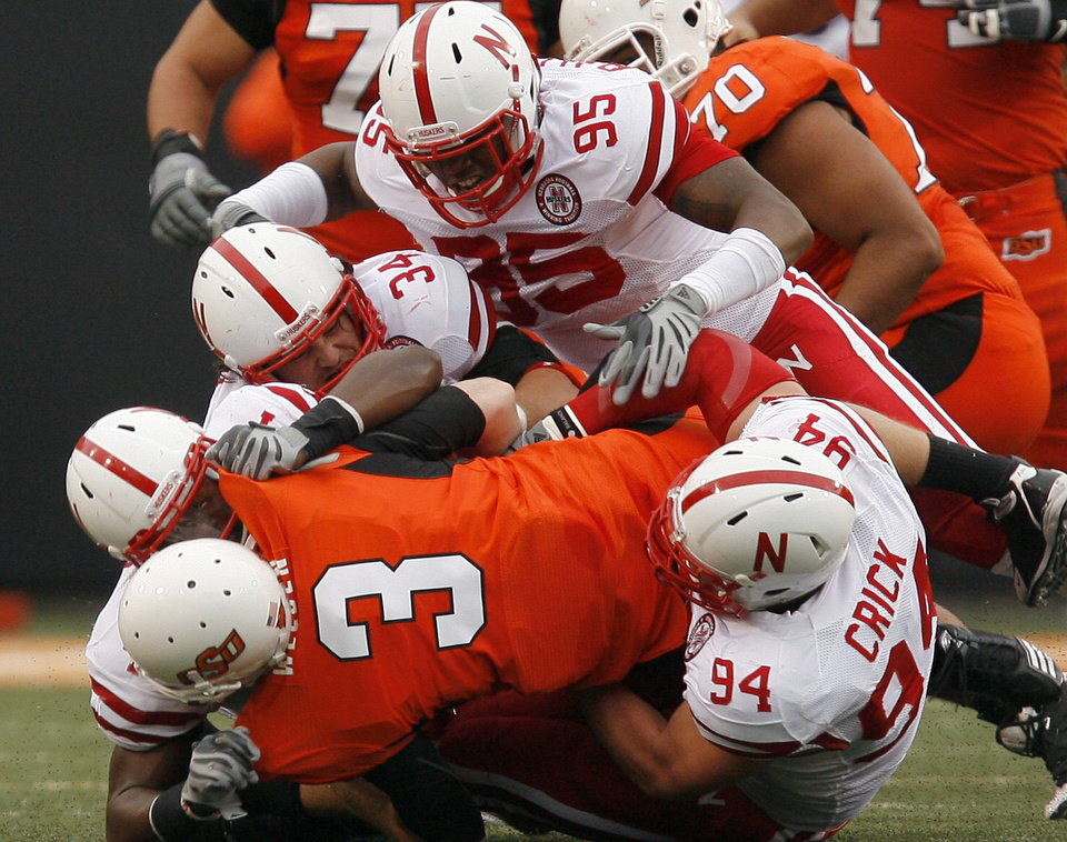 Photo - OSU's Brandon Weeden is sacked by a host of Nebraska defenders during the college football game between the Oklahoma State Cowboys (OSU) and the Nebraska Huskers (NU) at Boone Pickens Stadium in Stillwater, Okla., Saturday, Oct. 23, 2010. Photo by Sarah Phipps, The Oklahoman