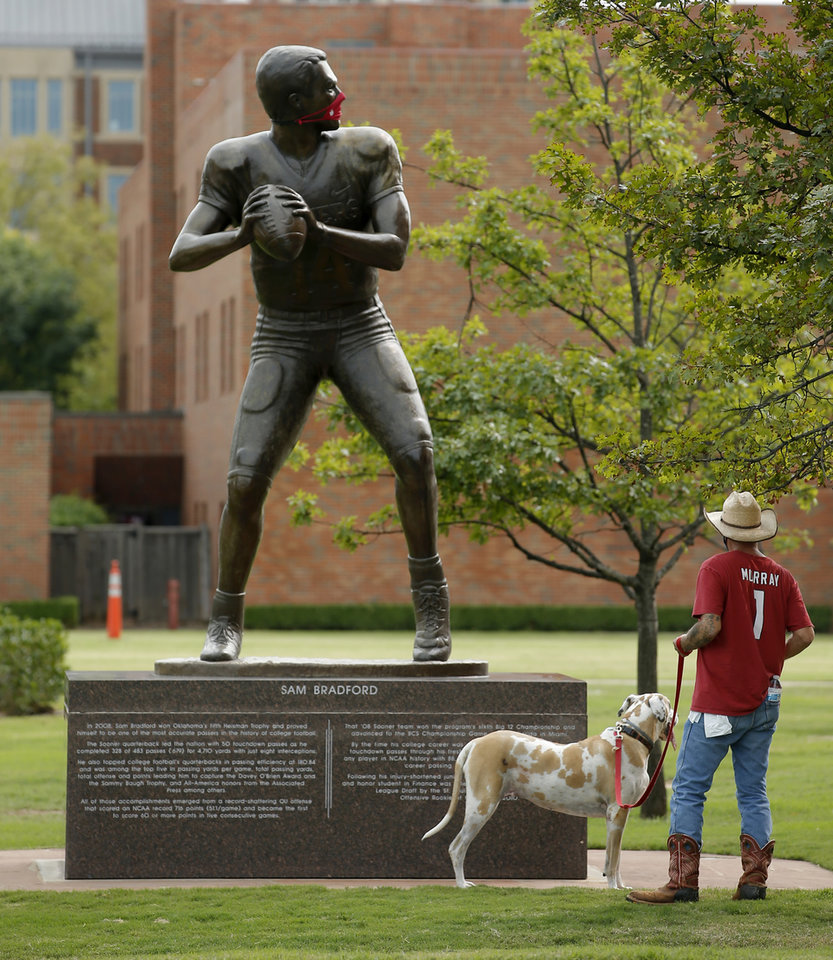 Photo - A man looks a statue of Sam Bradford at Heisman Park before a college football game between the University of Oklahoma Sooners (OU) and Missouri State in Norman, Okla., Saturday, Sept. 12, 2020. [Bryan Terry/The Oklahoman]