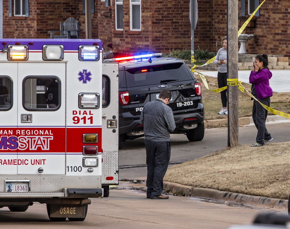 Photo - People react as emergency crews respond to a scene where six Moore High School students were hit by a truck killing one in Moore, Okla. on Monday, Feb. 3, 2020.  [Chris Landsberger/The Oklahoman]