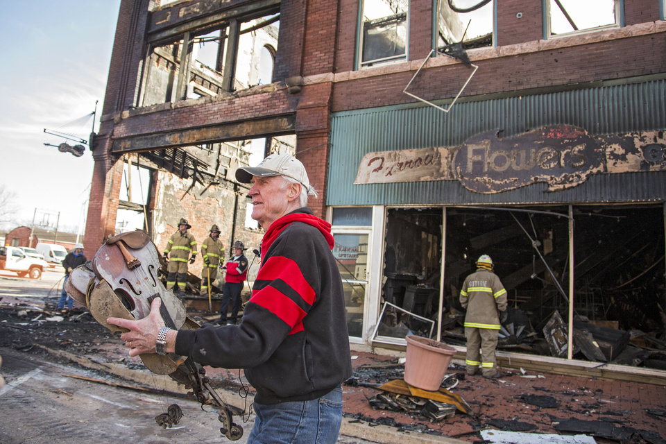 Photo - Fiddle player Byron Berline carries out damaged items from his fiddle shop that was destroyed by a fire in Guthrie, Okla. on Monday, Feb. 25, 2019. The fire on Saturday destroyed two businesses in historic downtown Guthrie.   Photo by Chris Landsberger, The Oklahoman