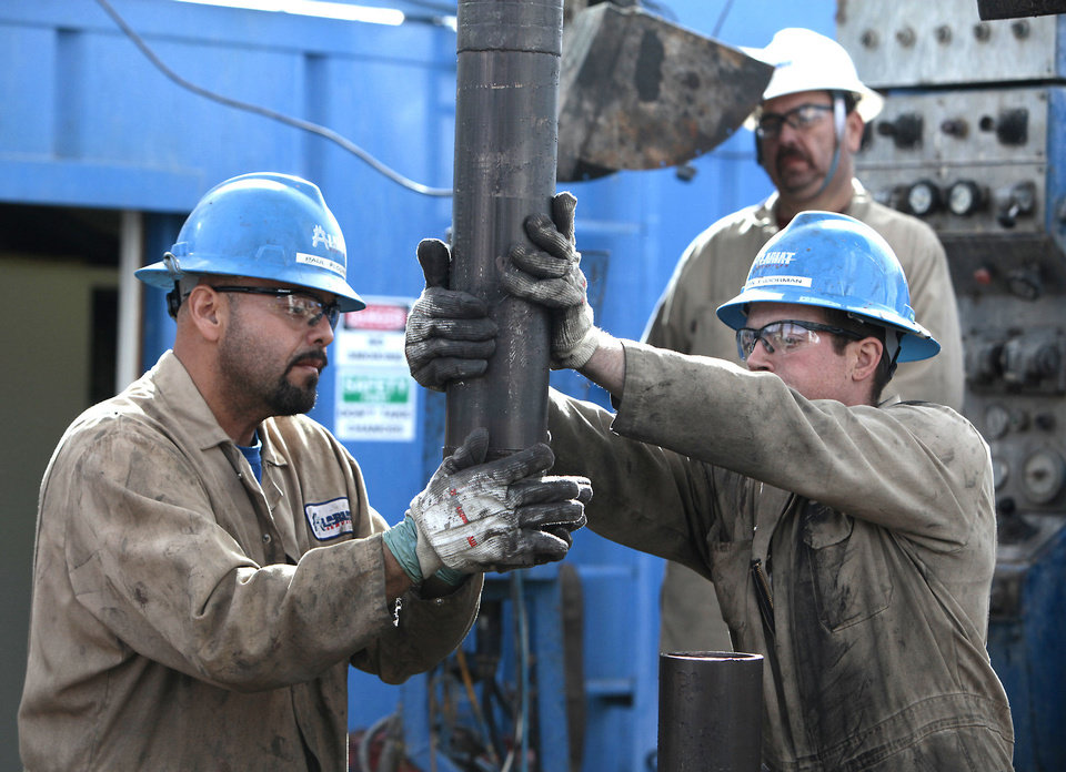 Photo - Floorman Paul Tabarez and Justin Stanfill place a cap on the end of a piece of drilling pipe being pulled on a SandRidge oil drilling rig near Medford.   Photo By David McDaniel, The Oklahoman Archives