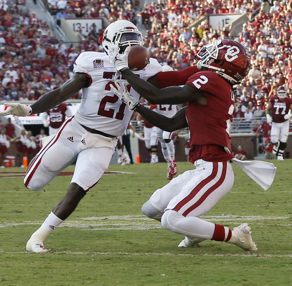 Photo - Oklahoma's CeeDee Lamb (2) makes a catch in front of South Dakota's Phillip Powell (21) in the first quarter during a college football game between the Oklahoma Sooners (OU) and South Dakota Coyotes at Gaylord Family - Oklahoma Memorial Stadium in Norman, Okla., Saturday, Sept. 7, 2019. [Nate Billings/The Oklahoman]