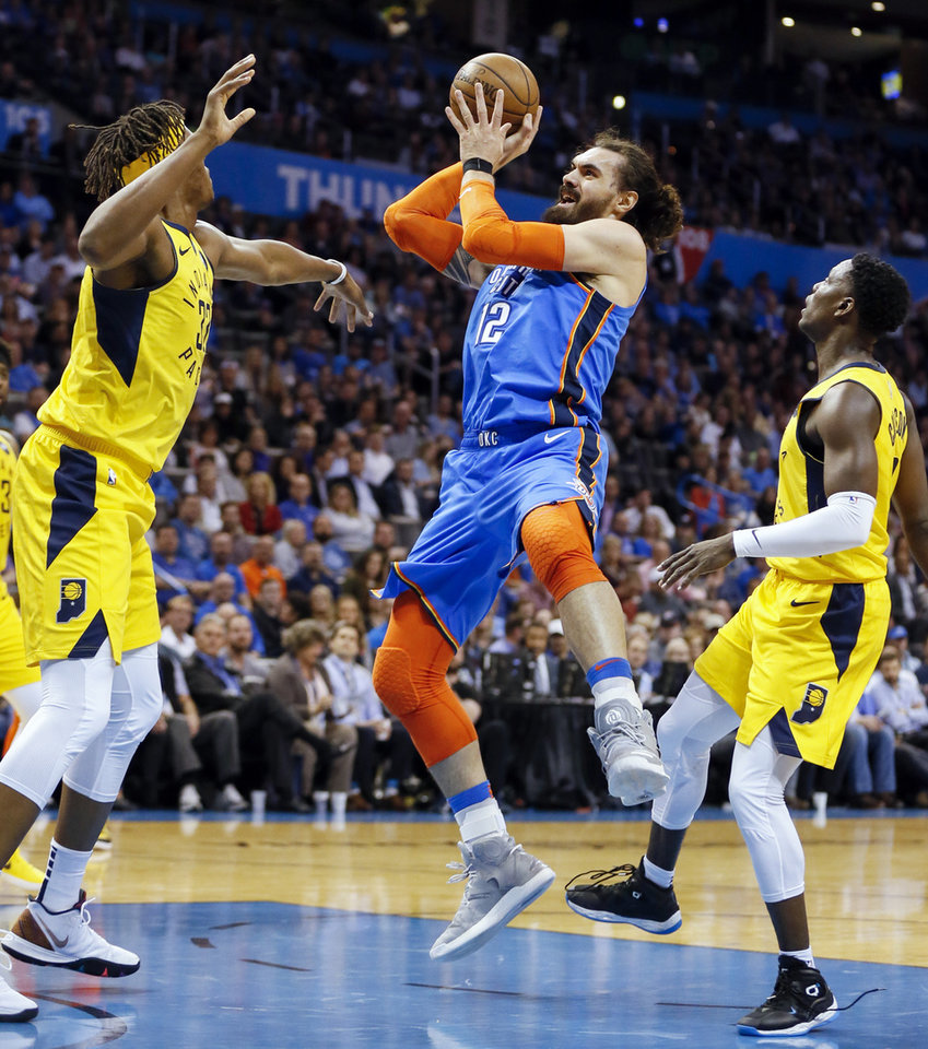 Photo - Oklahoma City's Steven Adams (12) shoots between Indiana's Myles Turner (33), left, and Darren Collison (2) during an NBA basketball game between the Indiana Pacers and the Oklahoma City Thunder at Chesapeake Energy Arena in Oklahoma City, Wednesday, March 27, 2019. Photo by Nate Billings, The Oklahoman