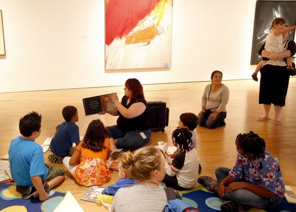 Photo - Mary Sholly reads a book to children during Free Family Day at the Oklahoma City Museum of Art, Sunday, Sept. 7, 2014. [Sarah Phipps/The Oklahoman Archives]