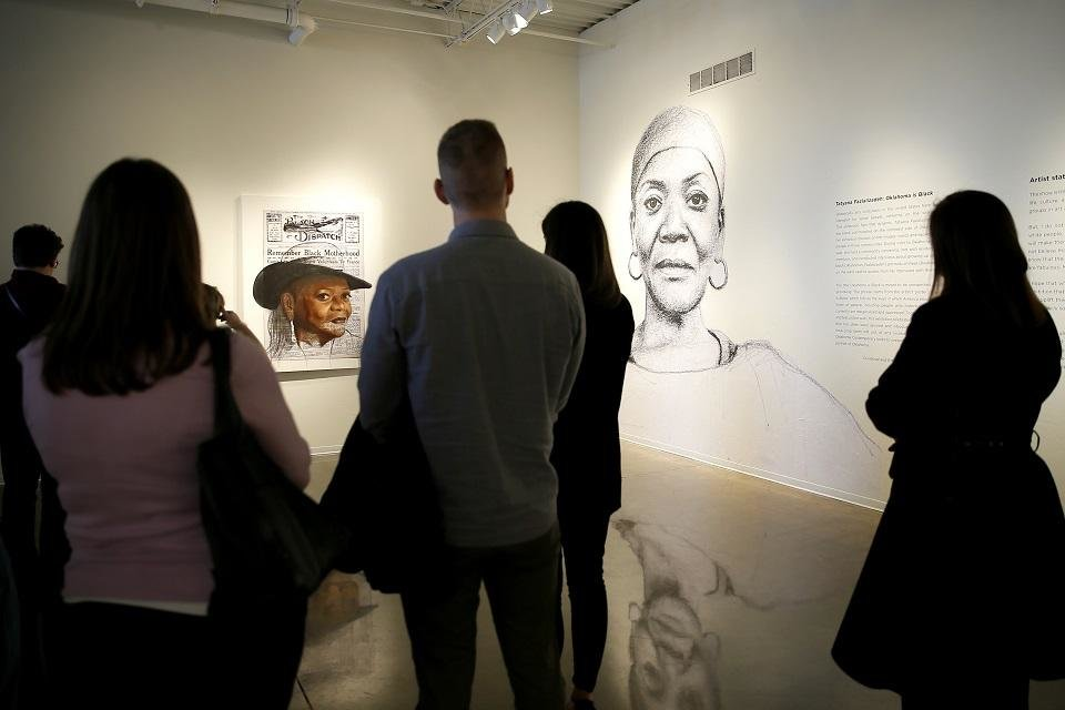 Photo - People looks at large-scale wheatpaste drawings in the exhibit