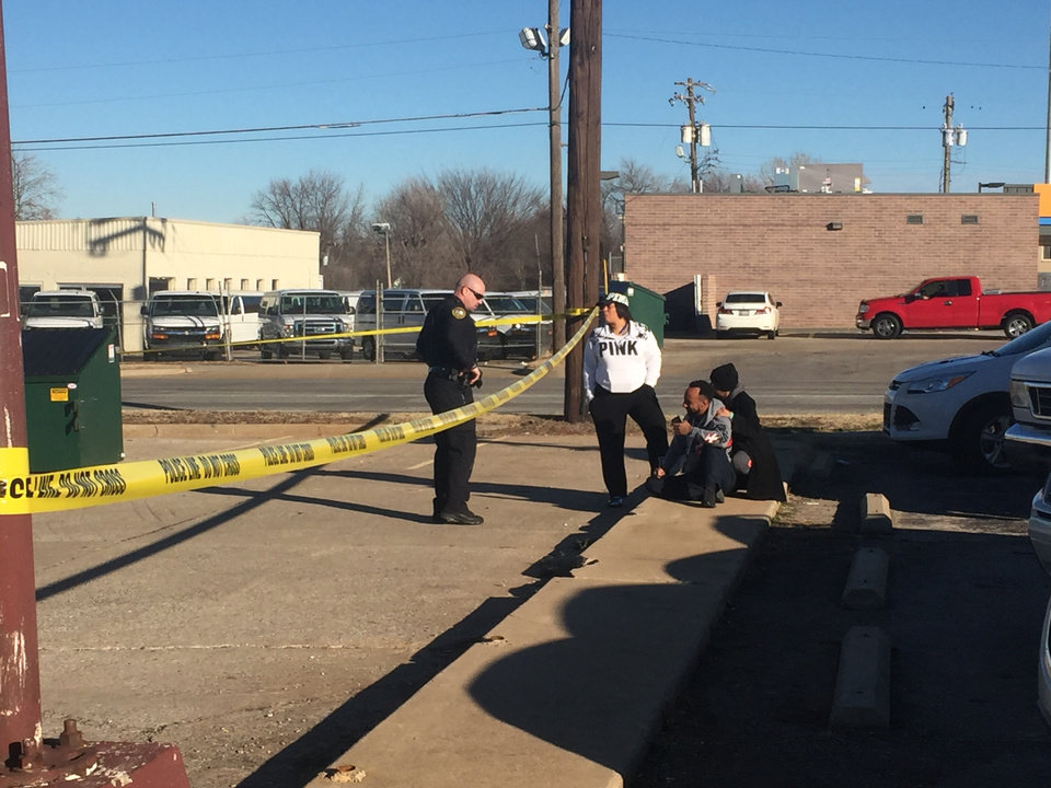 Photo -  A man arrived at the scene of a double homicide in Del City and was told to stay behind yellow crime scene tape after an officer told him a woman was dead inside Laundry Station, 4000 SE 15 Monday. Photo By Staff Writer Robert Medley