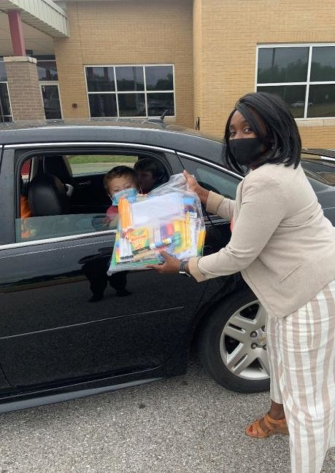 Photo -  Thanks to the Kit-A-Kid program, a student receives a package filled with school supplies provided by the Foundation for Oklahoma City Schools. [Photo provided]