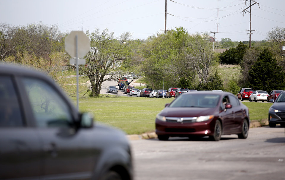 Photo - Traffic is pictured at North Kelley Ave., and E. Wilshire Blvd. near People's Church, 800 E. Britton Rd., in Oklahoma City, Thursday, April 9, 2020. Cars lined up for miles for hours as the church members gave away 6,000 pounds of free groceries and supplies. [Sarah Phipps/The Oklahoman]