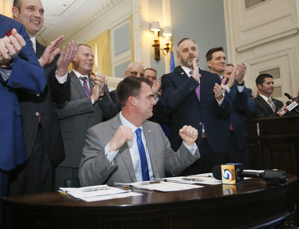 Photo -  Gov. Kevin Stitt raises his fists after signing five bills that would give him the authority to hire and fire the heads of five state agencies and to appoint or dismiss members of their boards, in the Blue Room at the state Capitol in Oklahoma City, Wednesday, March 13, 2019. [NATE BILLINGS/THE OKLAHOMAN]