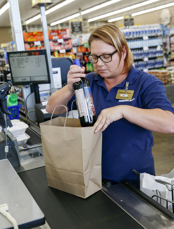 Photo -  Amy Colbert bags a bottle of wine with other groceries inside the Homeland grocery store at Classen and NW 18 on the first day of wine and strong beer sales in grocery stores, in Oklahoma City, Monday, Oct. 1, 2018. [Nate Billings/The Oklahoman]