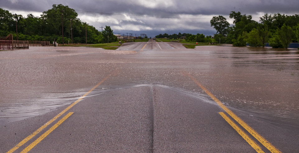 Photo - A flooded portion of Route 66 in El Reno, Okla. after heavy rains flooded the area on Tuesday, May 21, 2019.  [Chris Landsberger/The Oklahoman]