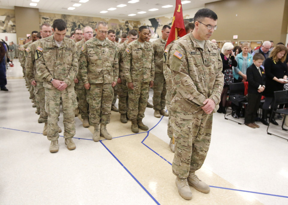 Photo -  Top: Capt. Randy Wright, commander of the 158th Field Artillery Unit, bows his head in prayer Friday during an Oklahoma Army National Guard homecoming ceremony for Battery B, 1st Battalion, 158th Field Artillery, 45th Field Artillery Brigade in Mustang.    Steve Gooch -