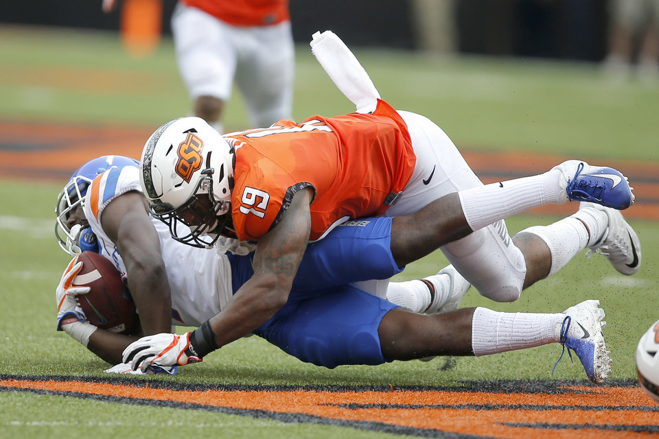 Photo - Oklahoma State's Justin Phillips (19) brings down Boise State's A.J. Richardson (7) during a college football game between the Oklahoma State University Cowboys (OSU) and the Boise State Broncos at Boone Pickens Stadium in Stillwater, Okla., Saturday, Sept. 15, 2018. Oklahoma State won 44-21. Photo by Bryan Terry, The Oklahoman
