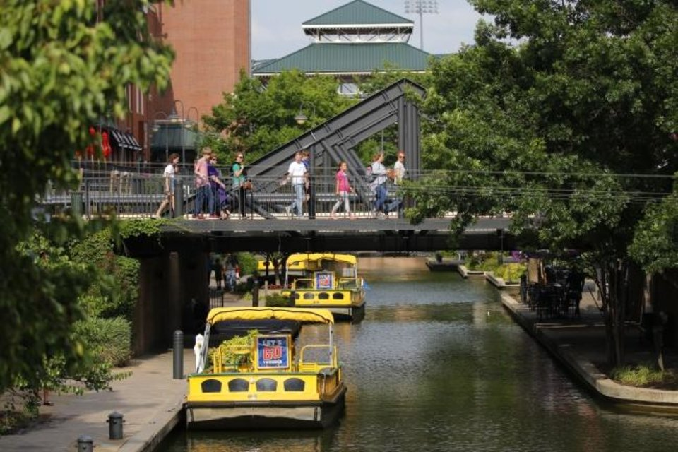 Photo -  A lush tree canopy provides shade along the Bricktown Canal where water taxis travel between basements of century-old buildings that were opened up as restaurants and bars when the waterway was excavated 20 years ago. [Doug Hoke/The Oklahoman]