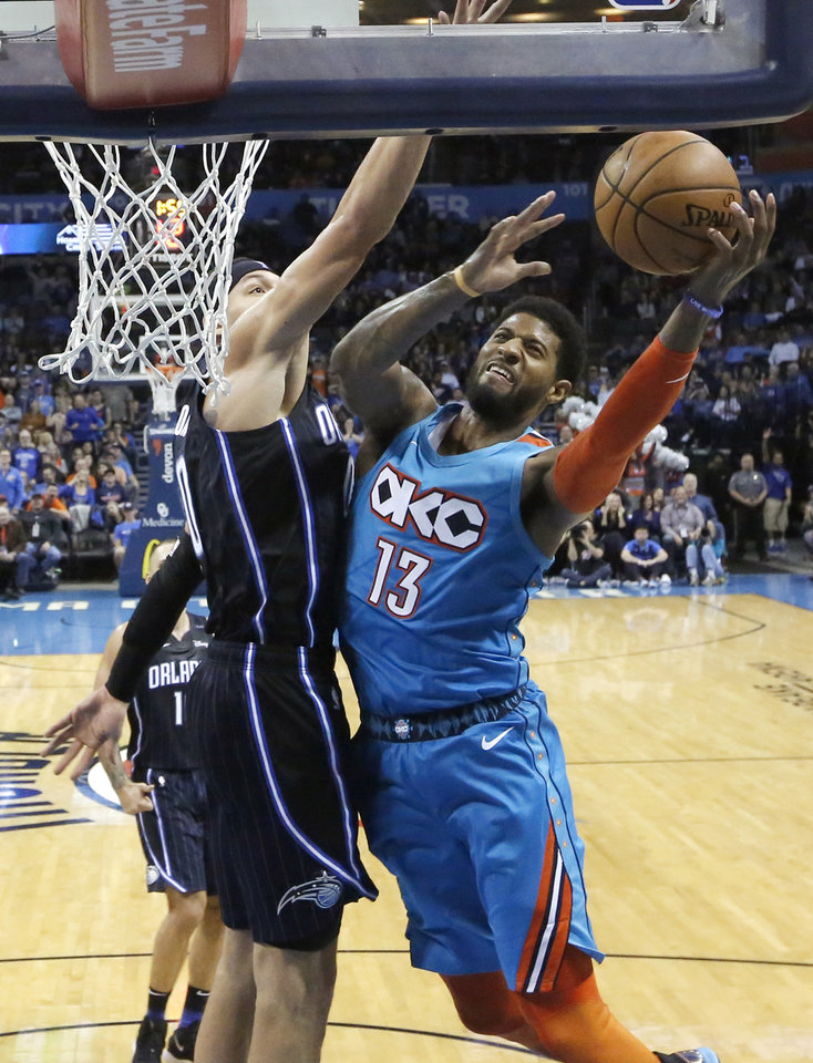 Photo - Oklahoma City's Paul George (13) goes up for a basket as Orlando's Evan Fournier (10) defends during the NBA game between the Oklahoma City Thunder and the Orlando Magic at the Chesapeake Energy Arena  Tuesday, Feb. 5, 2019. Photo by Sarah Phipps, The Oklahoman