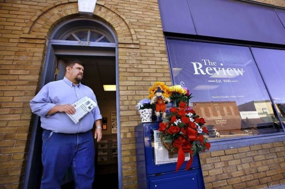 Photo - Todd Brooks stands in the doorway of the offices of the Marlow Review newspaper on Main Street in downtown Marlow on Tuesday, Oct. 14, 2014. Photo by Jim Beckel.