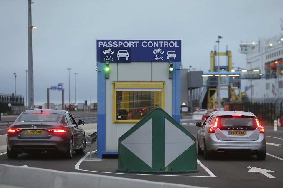 Photo -  Cars bearing British license plates stop at a passport control booth at the transit zone at the port of Ouistreham, Normandy, Thursday, Sept.12, 2019. France has trained 600 new customs officers and built extra parking lots arounds its ports to hold vehicles that will have to go through extra checks if there is no agreement ahead of Britain's exit from the EU, currently scheduled on Oct. 31. (AP Photo/David Vincent)