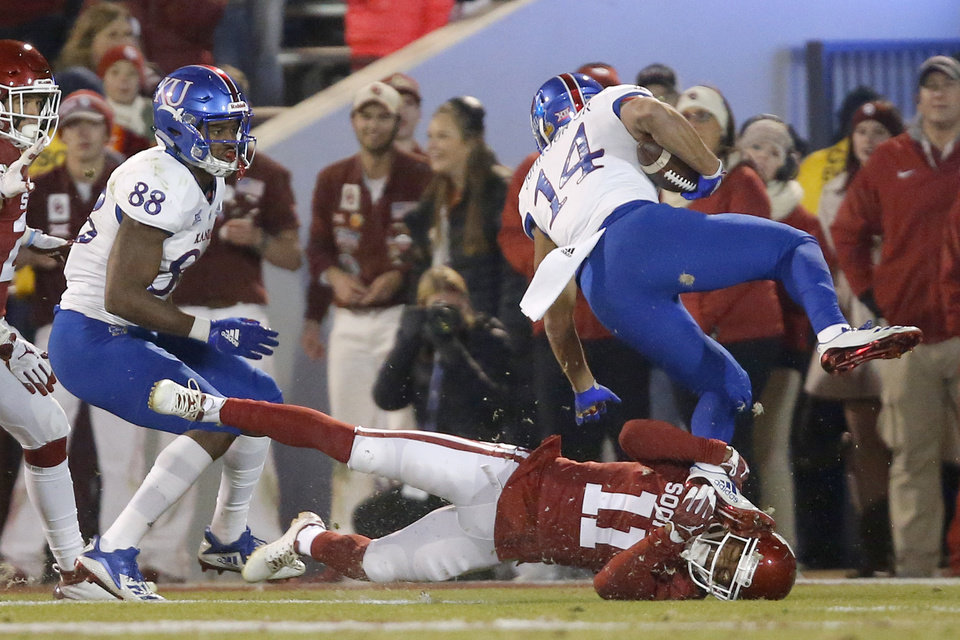 Photo - Oklahoma's Parnell Motley (11) tries to bring down Kansas' Kerr Johnson Jr. (14) during a college football game between the University of Oklahoma Sooners (OU) and the Kansas Jayhawks (KU) at Gaylord Family-Oklahoma Memorial Stadium in Norman, Okla., Saturday, Nov. 17, 2018. Photo by Bryan Terry, The Oklahoman