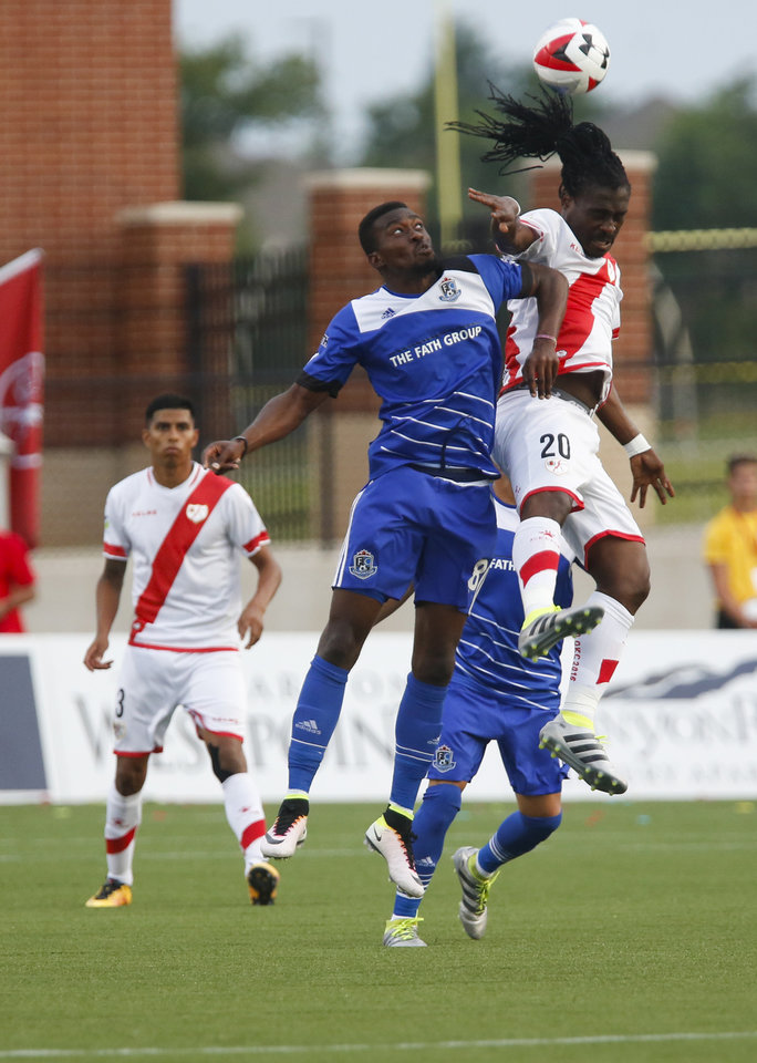 Photo - FC Edmonton's Tomi Ameobi (18) and Rayo OKC's Derek Boateng (20) both jump for the ball during a North American Soccer League game between Rayo OKC and FC Edmonton in Yukon, Okla., Saturday, July 2, 2016. The game ended in a 1-1 tie. Photo by Kurt Steiss, The Oklahoman