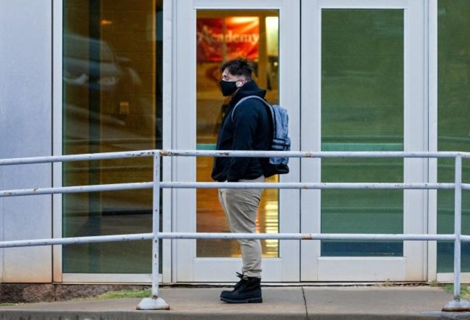 Photo -  A student waits in line to enter the building as students return to class at U.S. Grant High School in Oklahoma City, Okla. on Tuesday, Nov. 10, 2020. Students in grades first through 12th return to Oklahoma City Public Schools for the first time since March. The school district will have students attend in-person classes twice a week in a hybrid A/B schedule. [Chris Landsberger/The Oklahoman]