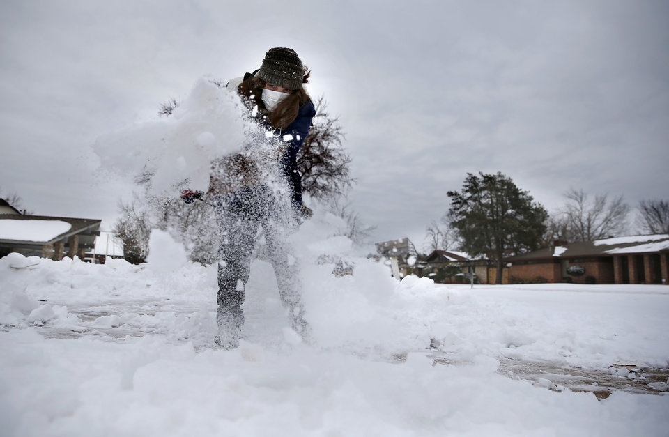 Photo - Kathy Alkhouri shovels snow from her driveway in northwest Oklahoma City, Tuesday, Feb. 16, 2021. [Sarah Phipps/The Oklahoman]